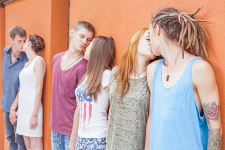 medium group: Medium group of young people kissing and standing in row near red wall background.