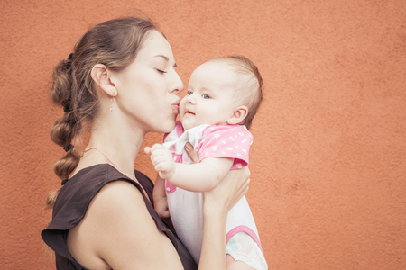 worl: Happy mother kissing her baby at wall background. Mother care is most important in baby life.