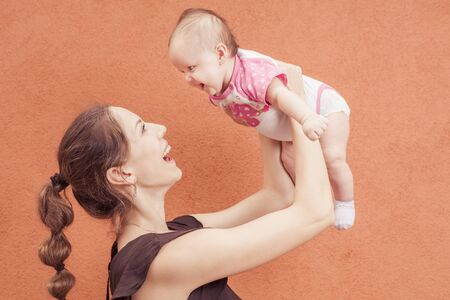 throw up: Happy young mother throw up baby on a background of orange wall. Child laughs in flight. Girl three months Stock Photo