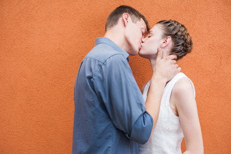 Kissing young couple at red wall background.