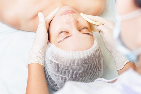 Beautiful young woman in spa salon receiving face treatment at white background. Concept of beauty, massage, healthy therapy  and relaxing at luxury resort