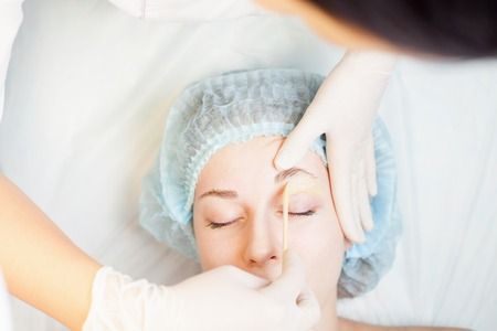 threading hair: Professional woman at spa beauty salon doing epilation or correction eyebrow using sugar  - sugaring. You can see her smooth eyebrow after hair removal Stock Photo