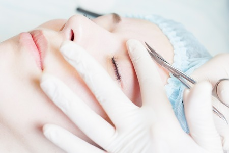 nail scissors: Professional woman at spa beauty salon doing correction and cuts eyebrow using nail scissors. You can see her smooth eyebrow after hair removal