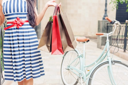 Closeup fashion woman dressed in striped dress with bags and vintage bike has shopping travel to Italy, Milan. She has happy vacation travel to Europe