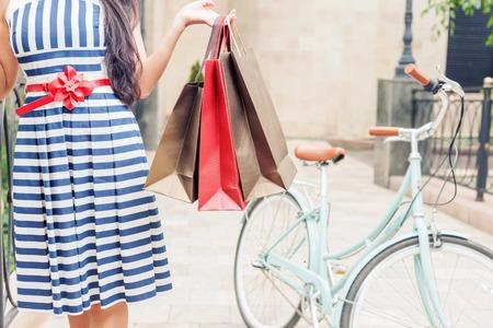Closeup Mode Frau in gestreiften Kleid mit Taschen und Vintage-Bike gekleidet hat Shopping Reisen nach Italien, Mailand. Sie hat glücklich Urlaubsreisen nach Europa Standard-Bild - 43739588