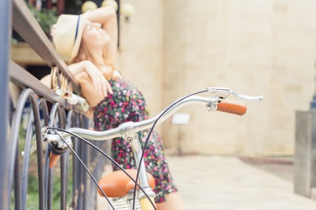 europe vintage: beautiful woman travel at europe by city vintage bicycle at summer time, she is dressed in elegant dress and standing on bridge at background. Selective Focus at bicycle handle at foreground Stock Photo
