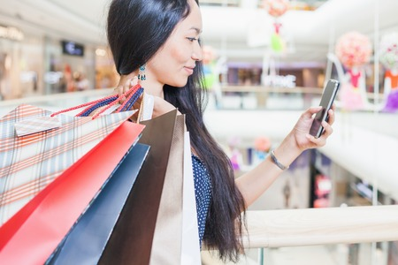 큰 쇼핑 센터 실내 휴대 전화를 사용 하여 가방과 함께 패션 아시아 여자. 그녀는 판매 및 할인에 대한 SMS를 받았습니다! 쇼핑 또는 쇼핑 몰, 판매 및 할