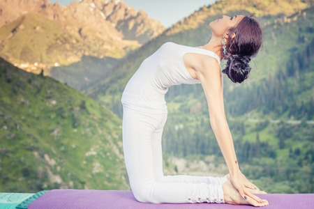 kundalini: Inspired asian woman doing exercise of yoga at mountain range of Kazakhstan. She dressed in white sportswear. Stock Photo
