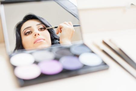 productos de belleza: maquillaje artista mujer que hace el maquillaje usando cepillo cosmético y espejo de aplicar sombra de ojos en los párpados por sí mismo en el salón de belleza con el fondo blanco