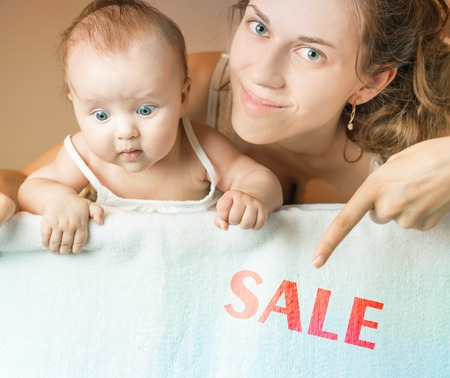 discount banner: Mom and baby lying on white blanket. Advertising banner sign - Mom is pointing down on text with word discount. Child stares down at inscription. Mother smiling and looking at camera Stock Photo