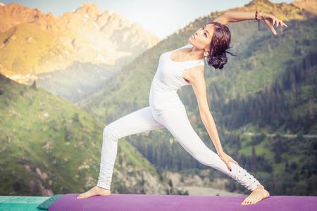 kundalini: Inspired asian woman doing exercise of yoga at mountain range of Kazakhstan. She dressed in white sportswear. Stock Photo