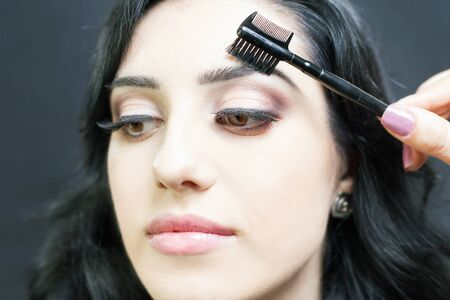 eyelids: makeup artist doing make up using cosmetic brush applying eye shadow on the eyelids for beautiful arabian and mixed race woman at beauty salon with black background Stock Photo