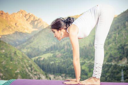 kundalini: Inspired asian woman doing exercise fold of yoga at mountain range of Kazakhstan. She dressed in white sportswear.