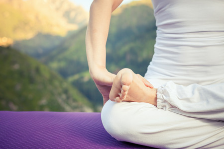 yoga meditation: Beautiful woman relaxing and meditating outdoor at swiss mountain. She sits at peak of mountain in lotus position and feel harmony of your body and nature. Healthy lifestyles concept of body and soul