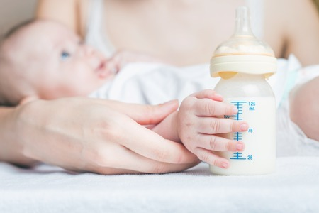 Baby mit einem Baby-Flasche mit der Muttermilch für das Stillen. Mütter Muttermilch ist die gesunde Ernährung für neugeborenes Baby. Standard-Bild - 43985741