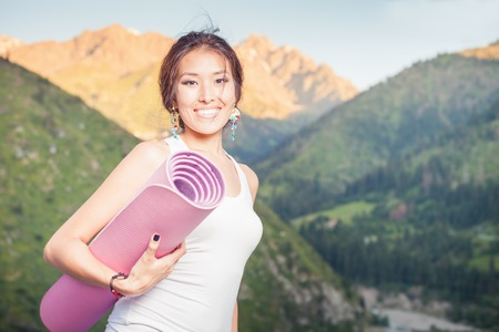 mat: Happy asian woman with yoga mat going to play in sports or fitness exercises outdoor at mountain. Healthy lifestyles concept of body and soul