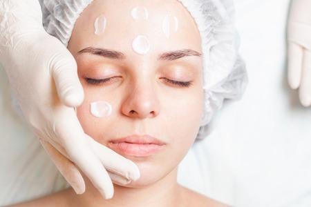 mujer maquillandose: Joven y bella mujer en salón spa recibiendo tratamiento facial con crema facial en el fondo blanco. Concepto de belleza, masaje, terapia saludable y relajante