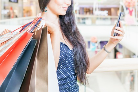 Fashion asian woman with a bag using mobile phone at big shopping center indoor. She received sms about sale and discount! Concept of shopping or shopaholic, sales and discounts at boutique