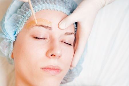 threading: Beautiful woman in spa salon receiving epilation or correction eyebrow using sugar  - sugaring. You can see her smooth eyebrow after hair removal Stock Photo