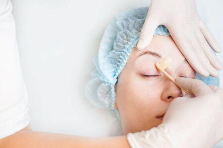 depilacion con cera: Mujer hermosa en el sal�n de spa recibir la depilaci�n o correcci�n de cejas usando az�car - adici�n de sacarosa. Usted puede ver la ceja suave despu�s de la depilaci�n
