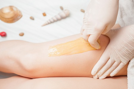 Sugaring epilation skin care with liquid sugar at legs. You can see her smooth and hair free armpits after hair removal. Stock Photo