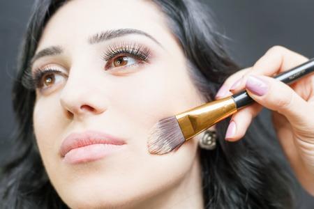 salon de belleza: Mujer árabe hermoso en el salón de belleza con un maquillaje agradable. Maquillaje artista aplicar la crema de fundación en el rostro, sosteniendo en las manos un brushe maquillaje sobre un fondo oscuro o negro.