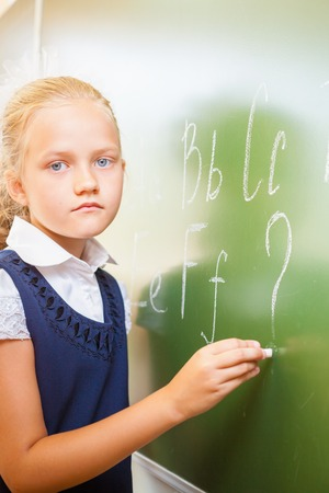 continuation: Schoolgirl writes English alphabet with chalk on a blackboard in school classroom. She looking at the camera and does not know continuation of the alphabet and wrote a question mark. Stock Photo