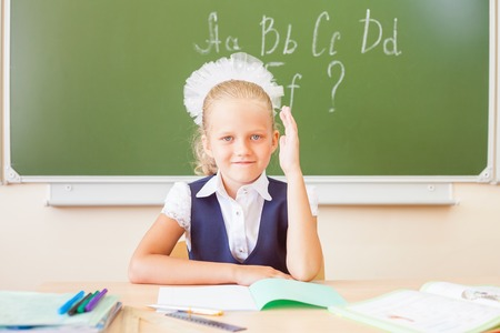 english girl: Girl sitting at the desk at school, on the background of the board, where she wrote the english alphabet. Schoolgirl raised her hand up. On the table lay a notebook, pen, pencil.