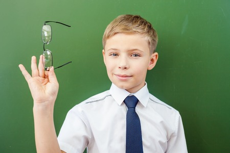 poor eyesight: Successful schoolboy standing near the blackboard in a school classroom, dressed in a school uniform, and holding medical glasses. Boys poor eyesight Stock Photo