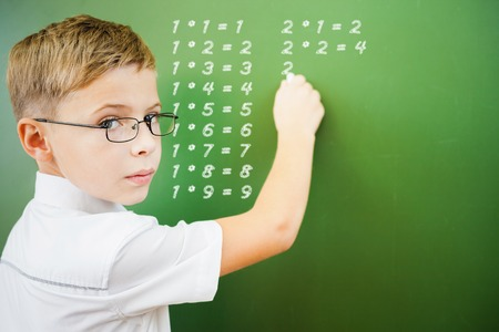 glass table: First grade schoolboy wrote multiplication table on blackboard with chalk at classroom and looking at the camera. Little boy dressed in a white shirt and wearing glasses. Concept of first of september