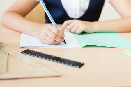 writing table: Desktop background of student sitting at a desk, holding a pen and ready to writing in a notebook for classwork or homework. On table there is a book, a copybook, a ruler, and copy space for text Stock Photo