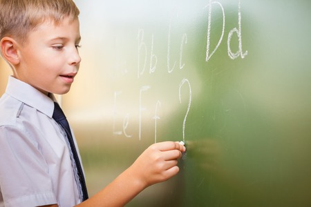 continuation: School boy writes English alphabet with chalk on a blackboard in school classroom. He does not know continuation of the alphabet and wrote a question mark.