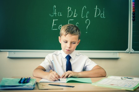 little table: Boy thinking and sits at a desk at school with glasses and writes in a notebook. Against the background of the school board english alphabet. Schoolboy dressed in a school uniform.