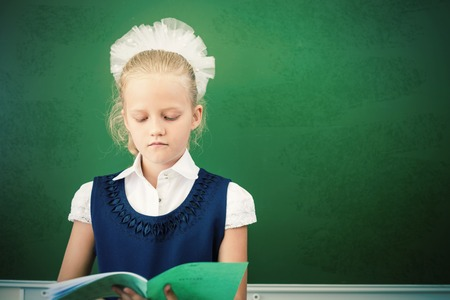first day: First grade schoolgirl holding a notebook at classroom. Little girl dressed in a school uniform. Concept of knowledge day and first of september. There is a copy space at green blackboard Stock Photo