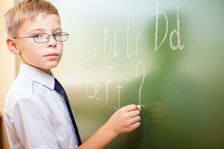 continuation: School boy writes English alphabet with chalk on a blackboard in school classroom. He looking at the camera and does not know continuation of the alphabet and wrote a question mark. Stock Photo