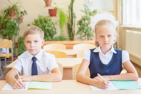 schoolroom: Students or classmates in school classroom sitting together at desk. They are dressed in school uniforms. On table there is a notebook and a pen. The class at background there are plants