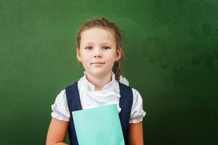 school notebook: First grade schoolgirl holding a notebook at classroom. Little girl dressed in a school uniform. Concept of knowledge day and first of september. There is a copy space at green blackboard Stock Photo