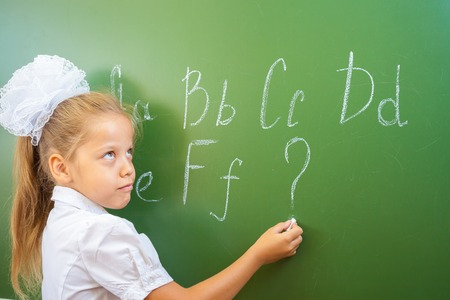 continuation: Schoolgirl writes English alphabet with chalk on a blackboard in school classroom. She does not know continuation of the alphabet and wrote a question mark.