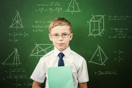 ni�o parado: Estudiante elegante o colegial con un bloc de notas, vestido con uniforme escolar y gafas de sol de pie cerca de la pizarra garabateadas con tiza - f�rmulas y dibujo. Concepto de un ni�o inteligente y cient�fico