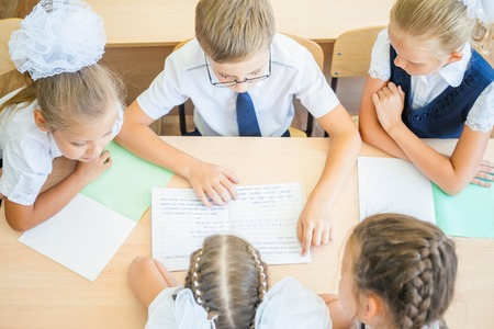 Group of schoolchildren or kids at school classroom sitting at a desk and help each other with their homework. Concept of teamwork among students, top view