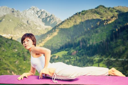 qigong: Inspired asian woman doing exercise of yoga at mountain range of Kazakhstan. She dressed in white sportswear. Stock Photo