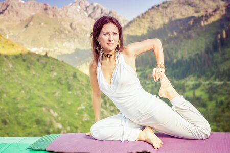 kundalini: Inspired woman doing exercise of yoga at mountain range of Kazakhstan. She dressed in white sportswear.