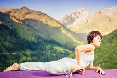 inspired: Inspired asian woman doing exercise of yoga at mountain range of Kazakhstan. She dressed in white sportswear. Stock Photo