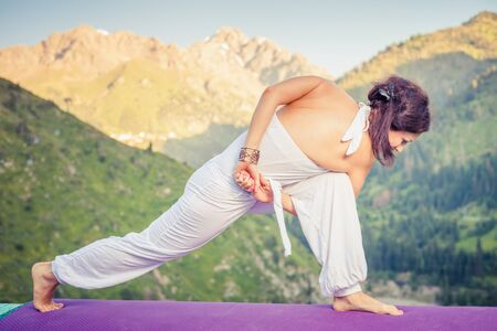 qigong: Inspired woman doing exercise of yoga at mountain range of Kazakhstan. She dressed in white sportswear. Selective focus on the hands