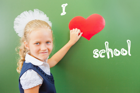 love very: School Girl holding the symbol of heart at the school classroom near the blackboard, there is written - I love school. Very important to teach children to love school. Welcome back to school! Stock Photo