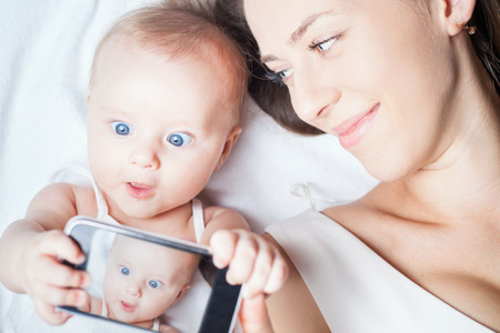 self care: Funny baby girl make selfie on mobile phone and lying near her mother on a white bed. Newborn looking at the camera and smiling. Mothercare is most important in baby life