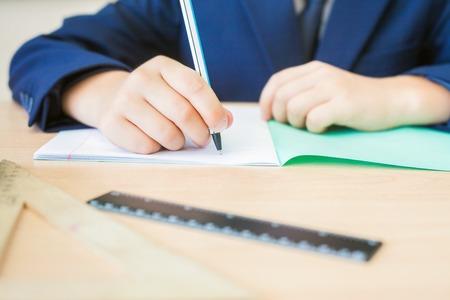 ni�os con l�pices: Fondo de escritorio del estudiante que se sienta en el escritorio, celebraci�n de l�piz y lista para escribir en un cuaderno de trabajo en clase o en casa. En la mesa hay cuaderno, regla. Concepto de primera septiembre y el d�a del conocimiento