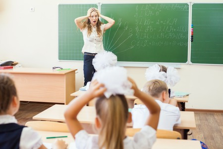 Teacher woman in stress or depression at school classroom, children or students driving her crazy.