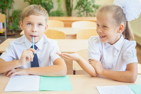 classwork: Students or classmates in school classroom sitting together at desk. Schoolboy thought, and girl helps him for the classwork. They are dressed in school uniforms. On table there is notebook and pen.