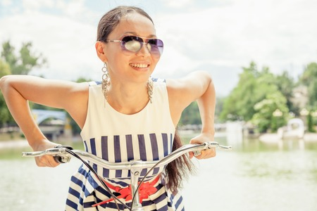 sombrero: Closeup happy fashion asian woman with sunglasses, travel to Paris by city bicycle, she looks amazing, delighted and enjoy her journey and looks into the camera Foto de archivo
